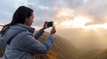 Woman taking photo on mountain